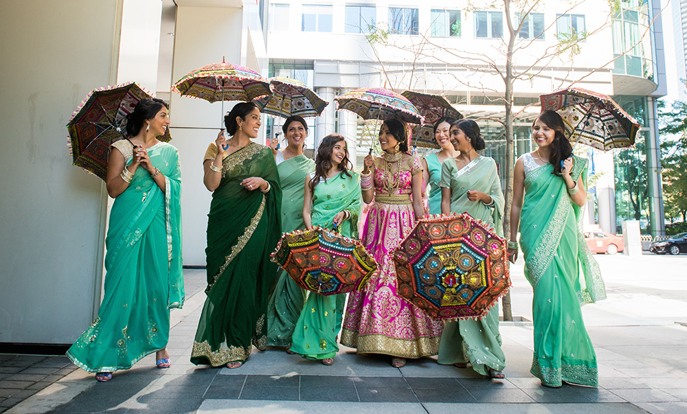 Indian bride in pink lehnga with her bridesmaids in green saris