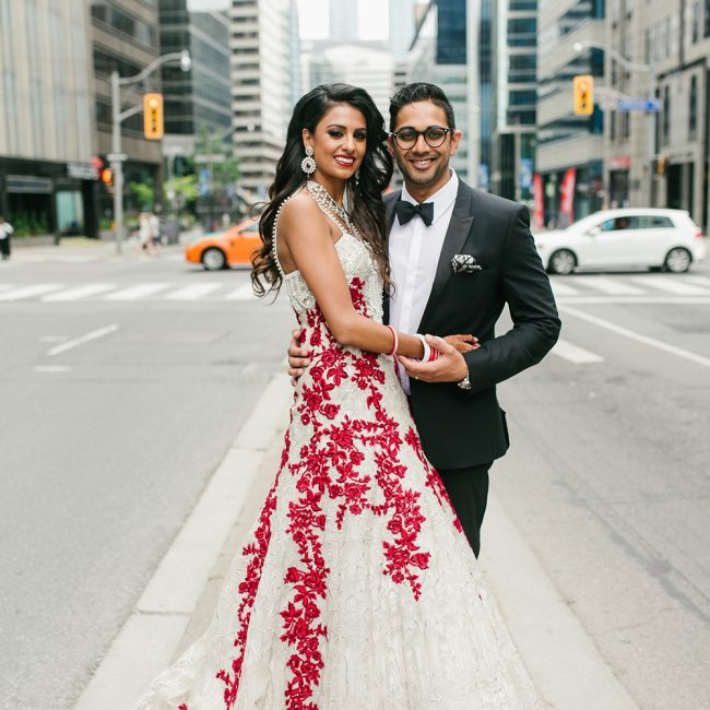 Modern Indian bride and groom posing downtown, bride in white and red wedding dress, groom in black tuxedo - Arora Events, Toronto's best wedding and event planners!