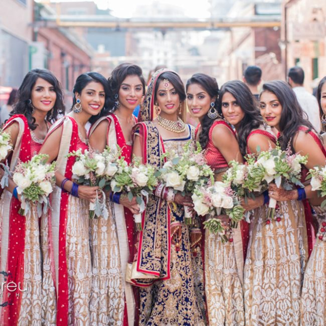 Indian bride and her bridesmaids in matching red and brown lehengas - Arora Events, Toronto's best wedding and event planners!