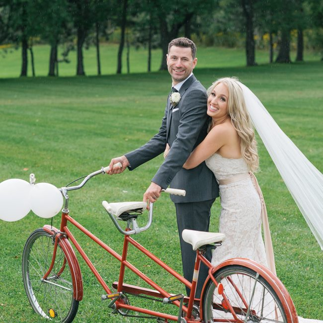 Bride and groom posing with a tandem bicycle - Arora Events, Toronto's best wedding and event planners!