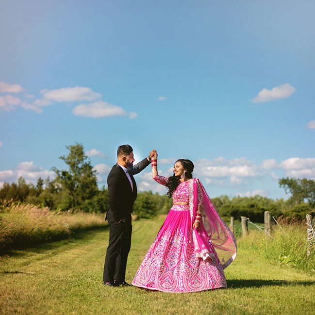 Indian bride in pink lehenga and groom in black tuxedo - Arora Events, Toronto's best wedding and event planners!