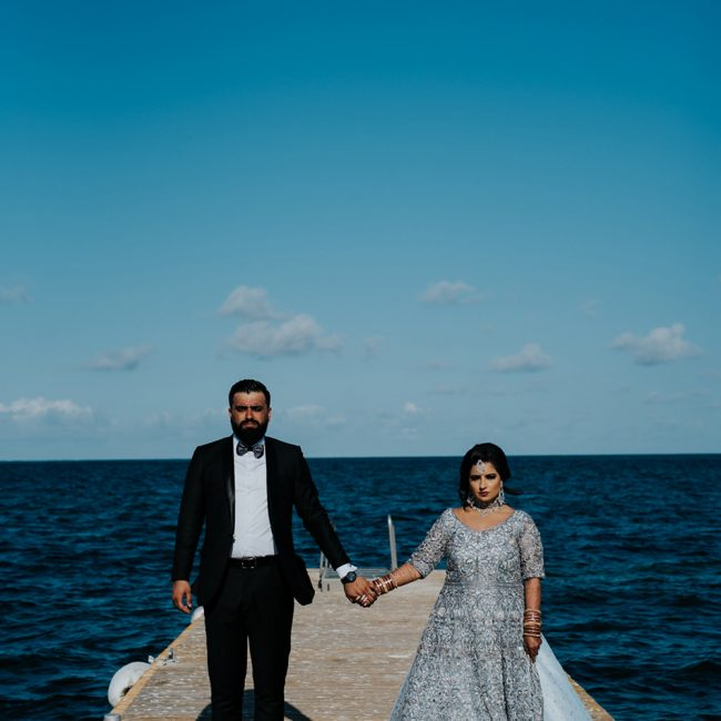 Indian bride and groom posing on a pier in a destination wedding - Arora Events, Toronto's best wedding and event planners!