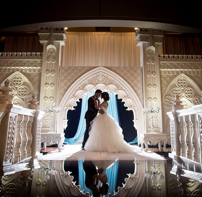 Couple standing in front of elaborate white stage. Arora Events, Toronto's best wedding and event planners!