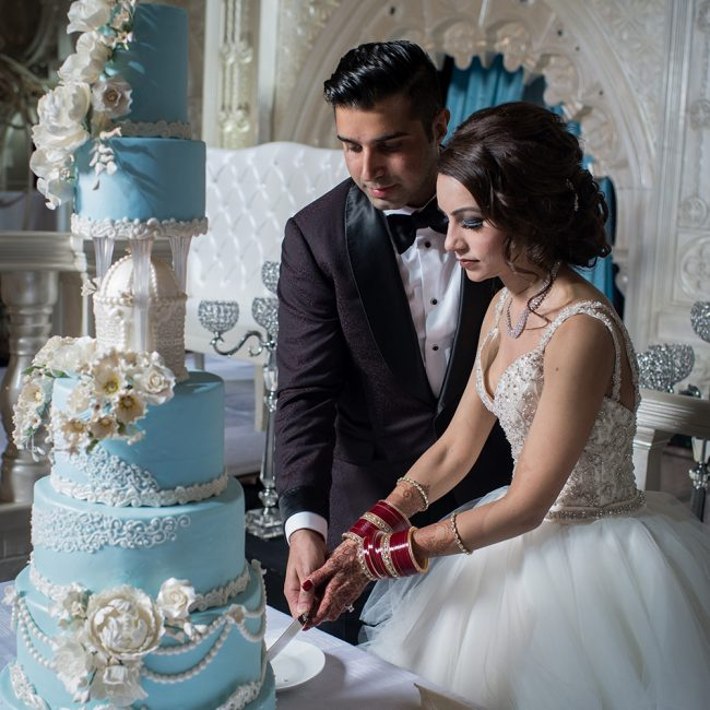 Indian couple cutting blue wedding cake - Arora Events, Toronto's best wedding and event planners!